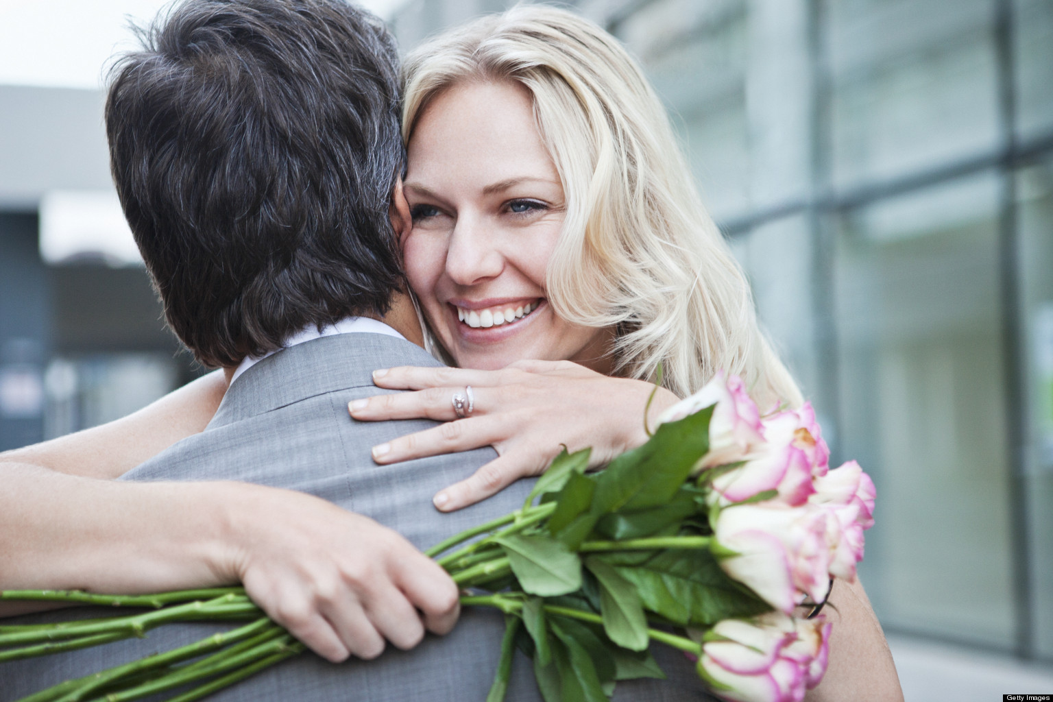 woman with roses, hugging man, smiling
